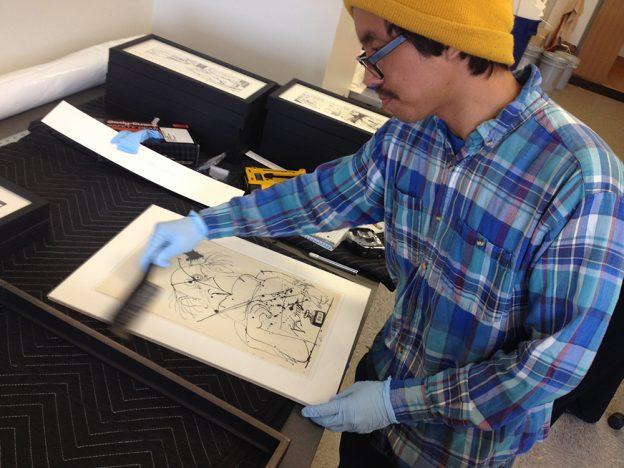 Justin Luna framing art for exhibition